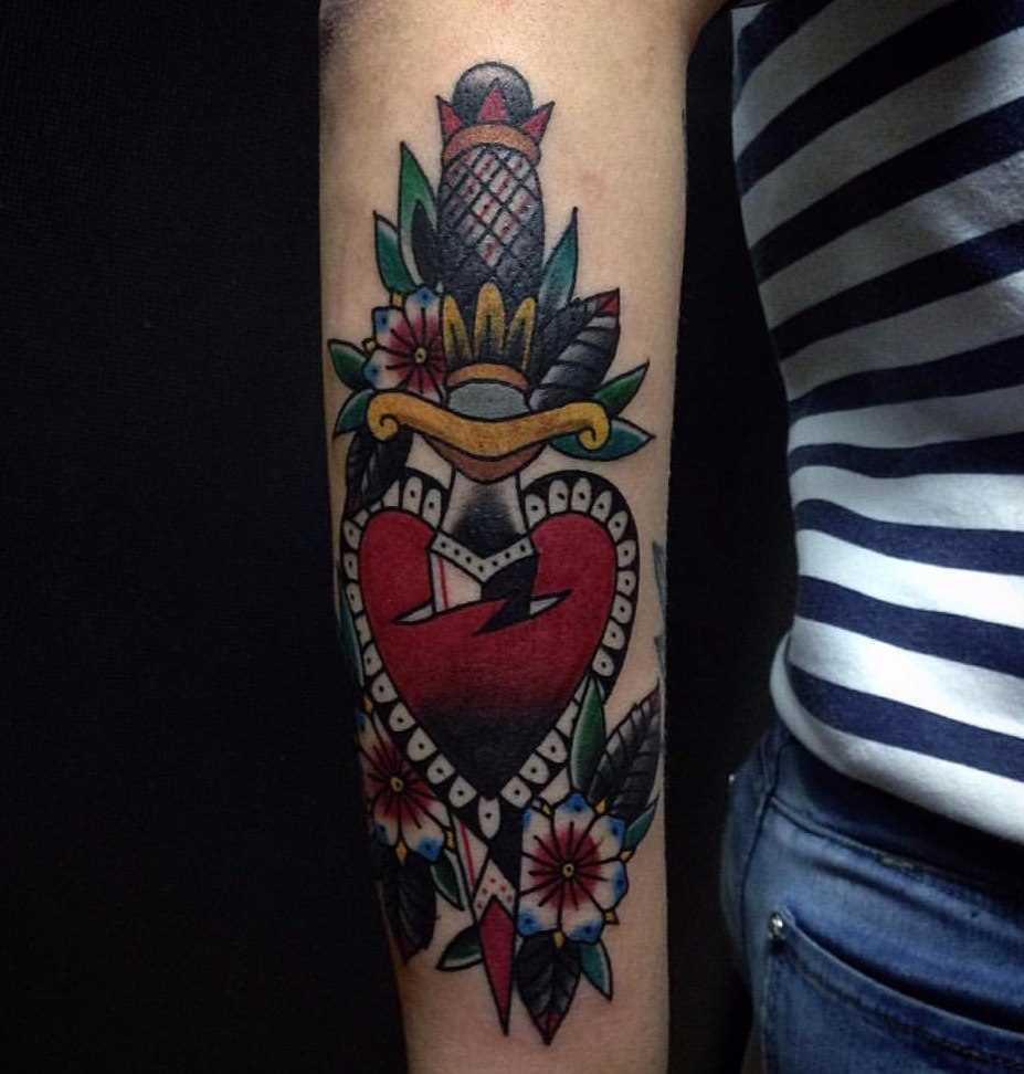 A tatuagem no estilo oldschool no antebraço de uma menina - o punhal e o coração