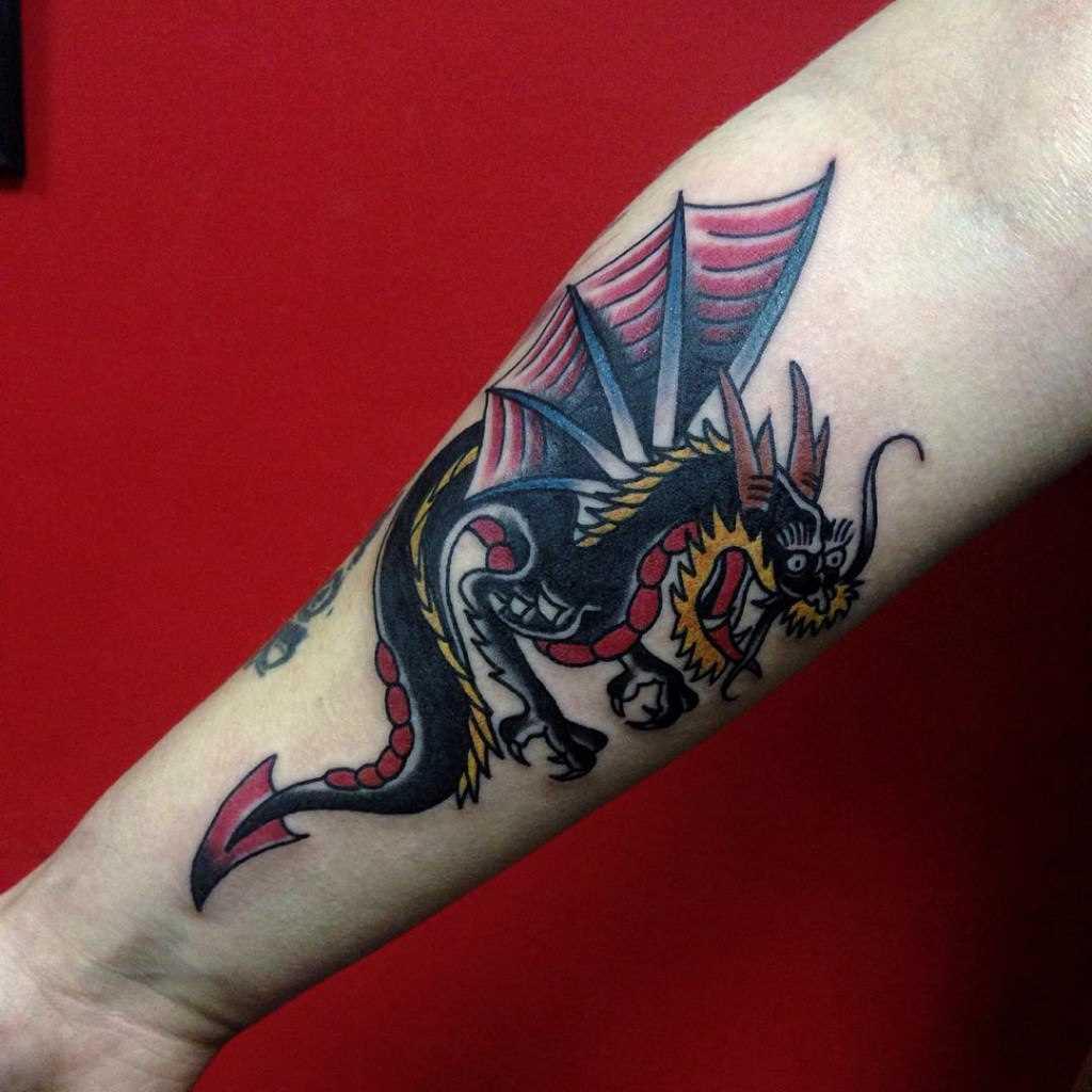 A tatuagem no estilo oldschool no antebraço garota -dragão