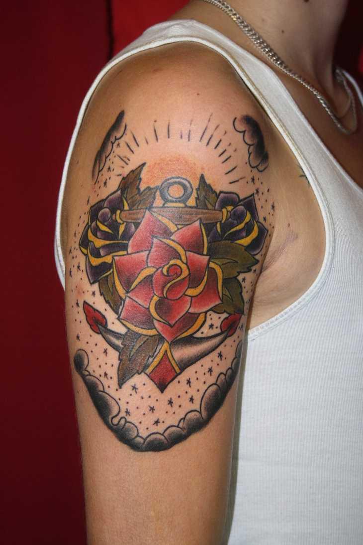 A tatuagem no estilo oldschool no ombro de um cara - de- rosas e âncora