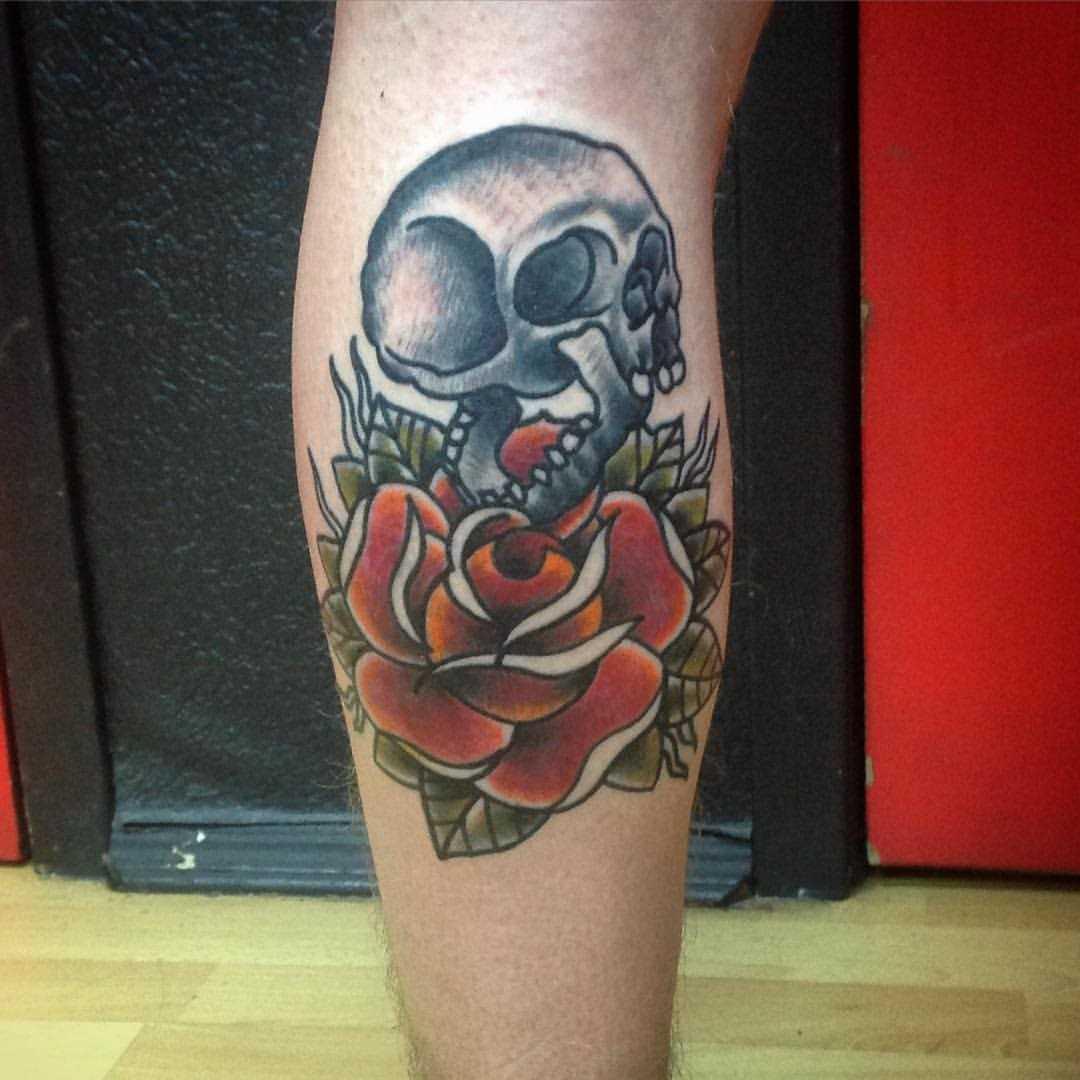 A tatuagem no estilo oldschool sobre a perna de um cara - de- rosa e o crânio