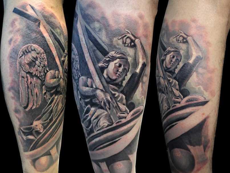A tatuagem no estilo realista sobre a perna de um cara - de- anjo com a cruz