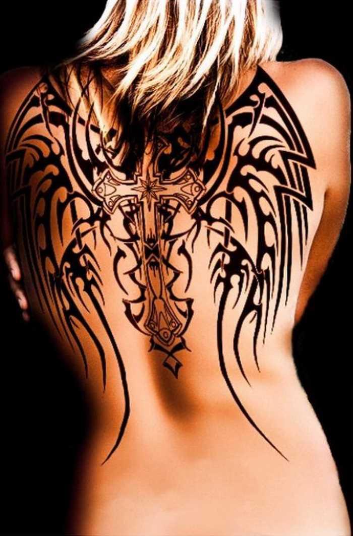 A tatuagem no estilo tribal nas costas da menina - cruz e asas