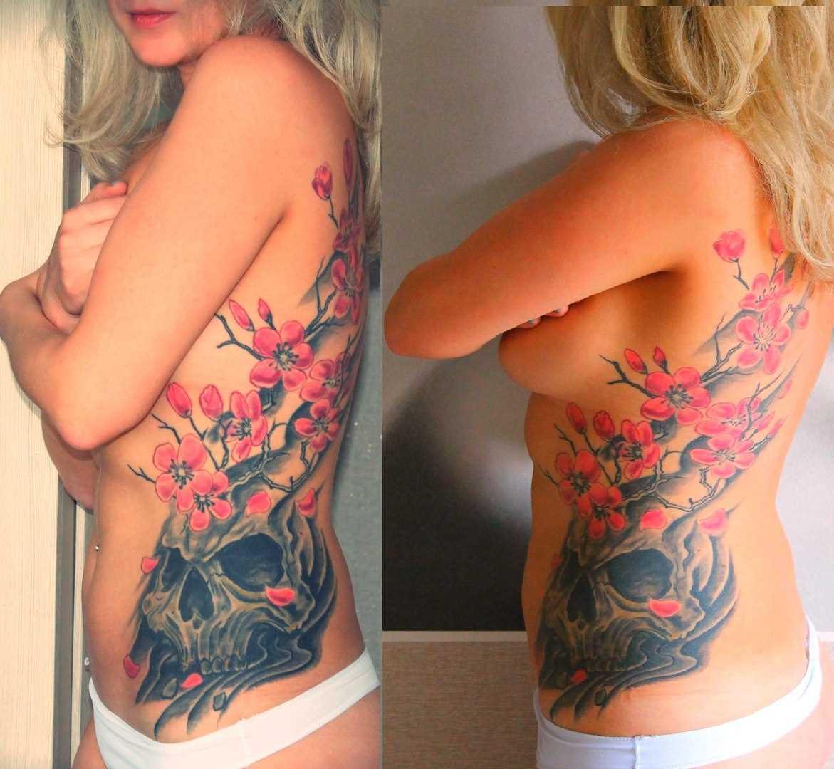 A tatuagem no lado da menina de crânio e sakura