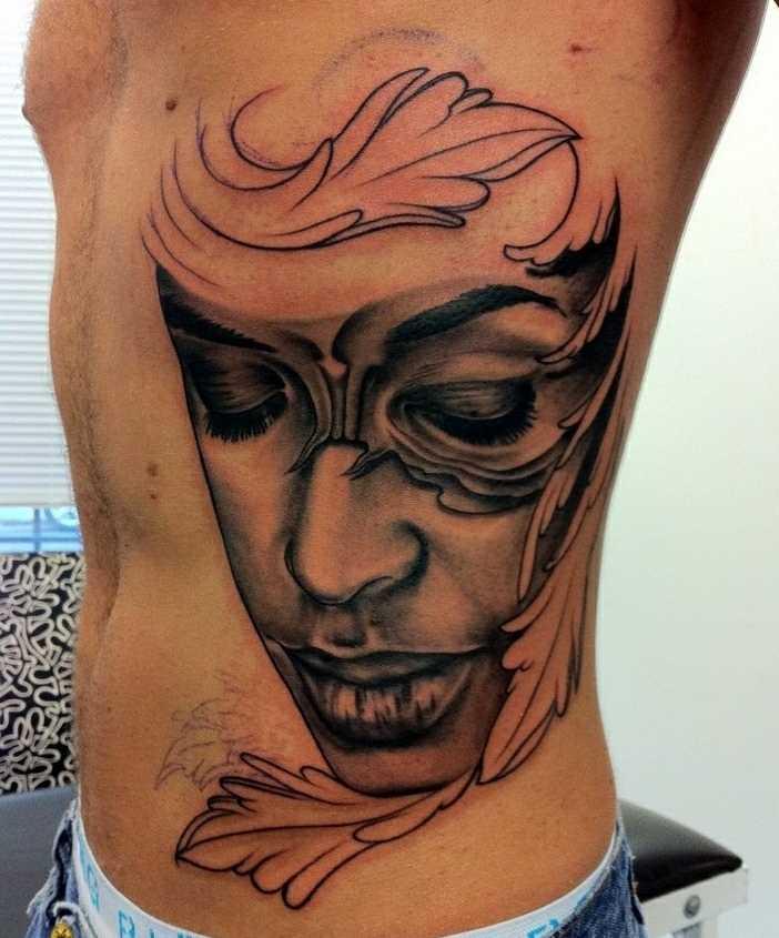 A tatuagem no lado de um cara - máscara