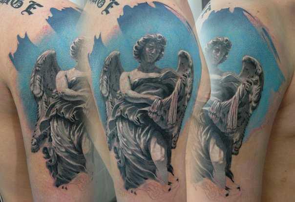 A tatuagem no masculino ombro - a estátua de um anjo