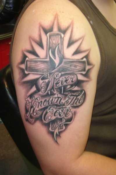A tatuagem no ombro da menina - a cruz e a inscrição