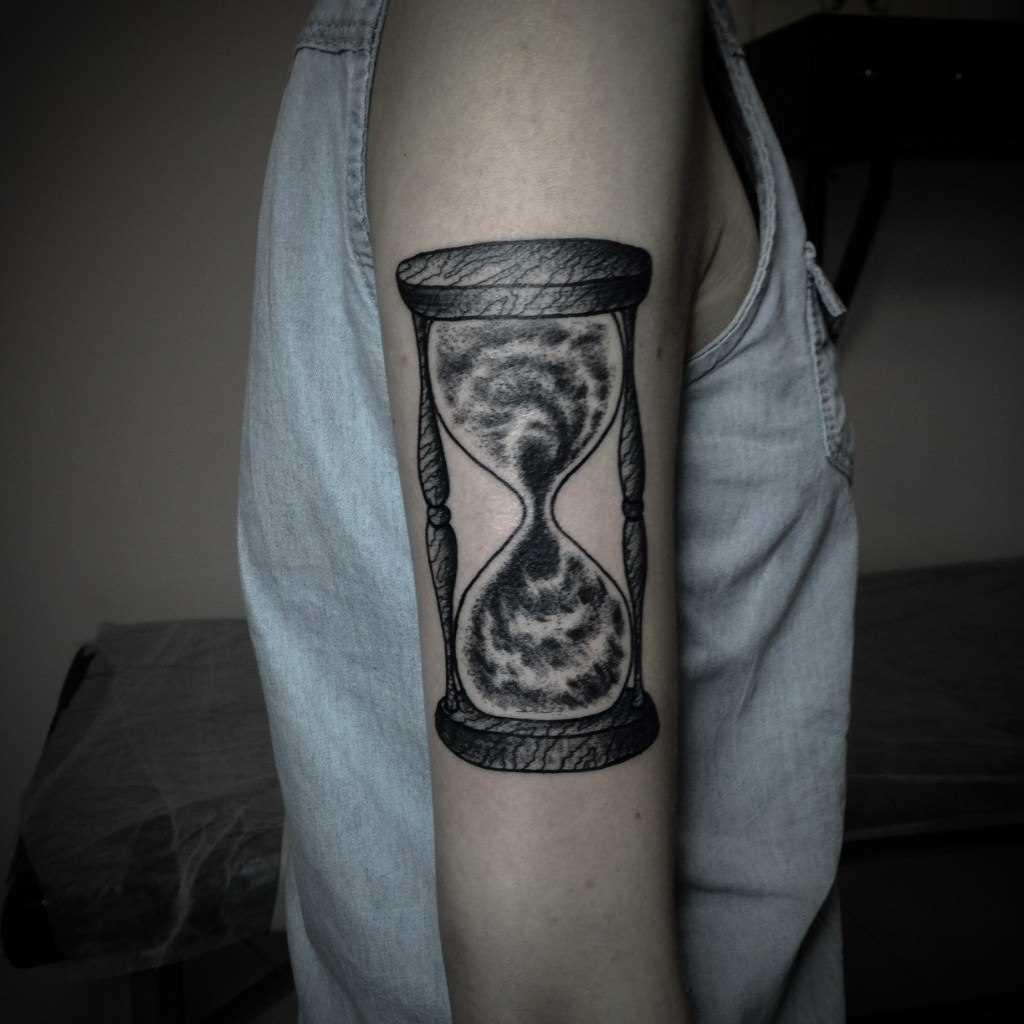 A tatuagem no ombro da menina - ampulheta