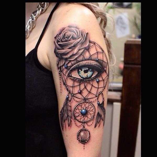 A tatuagem no ombro da menina - apanhador de sonhos, de olhos e rosa