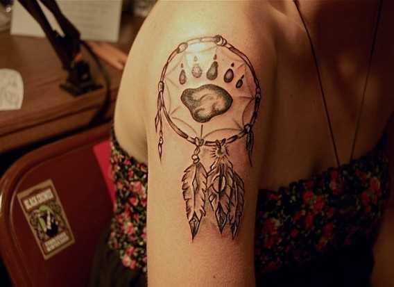 A tatuagem no ombro da menina - apanhador de sonhos e a flor