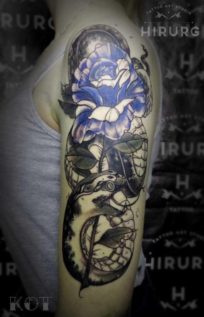 A tatuagem no ombro da menina de rosa e uma cobra