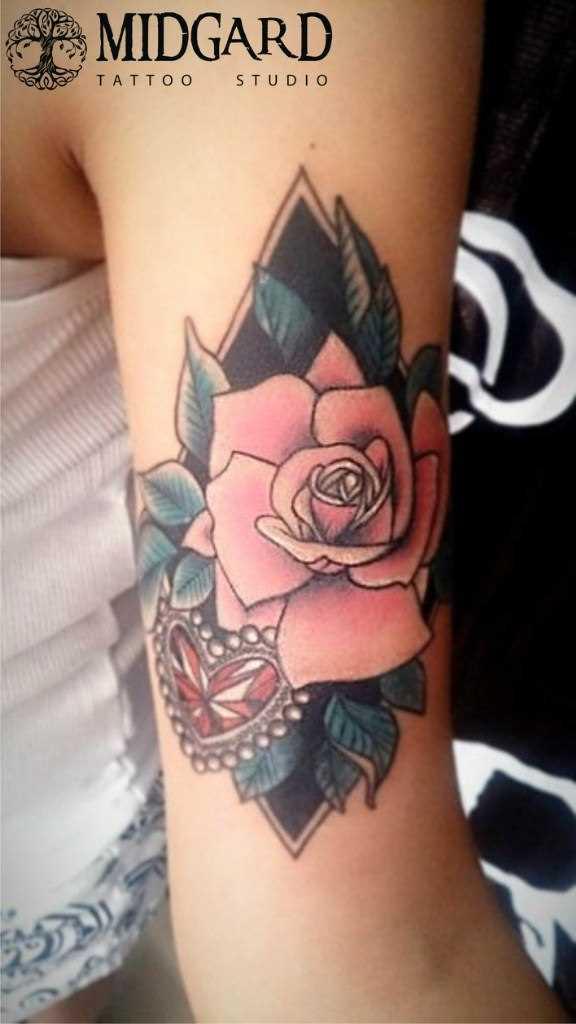 A tatuagem no ombro da menina - rosa e coração