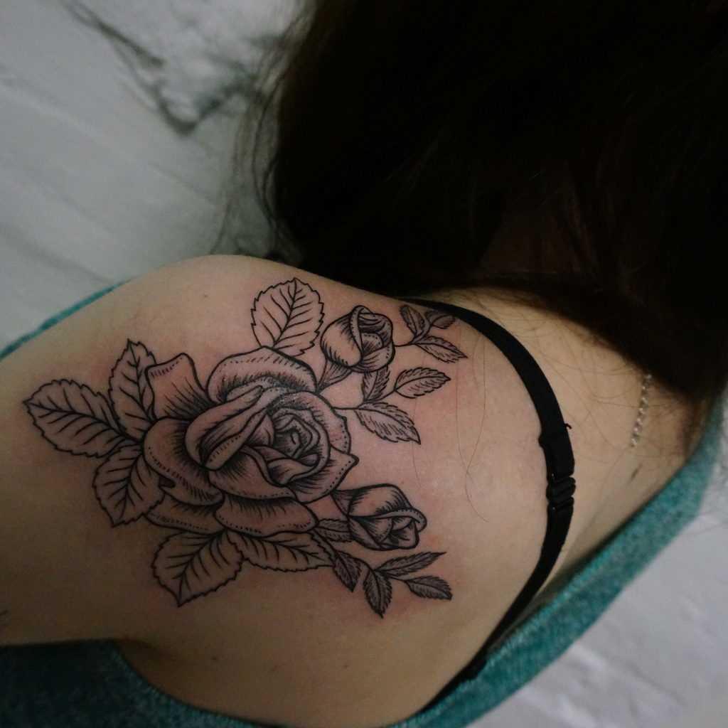 A tatuagem no ombro da menina - rosa em estilo lainvork