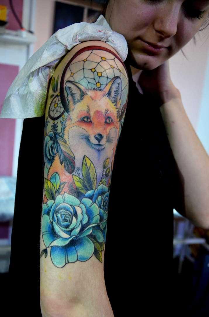 A tatuagem no ombro da menina - uma raposa, um apanhador de sonhos e rosa