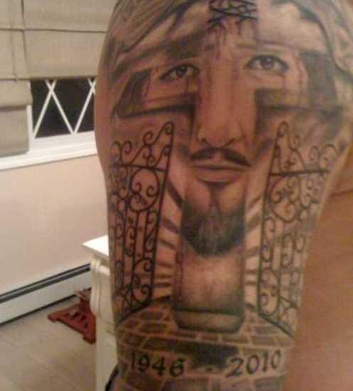 A tatuagem no ombro de um cara - a cruz e o rosto de Jesus, que ele