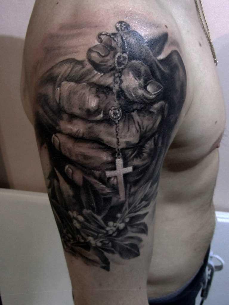 A tatuagem no ombro de um cara - a cruz nas mãos
