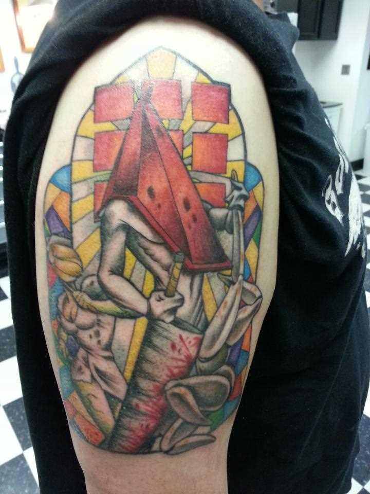 A tatuagem no ombro de um cara - a pirâmide em forma da cabeça de uma pessoa