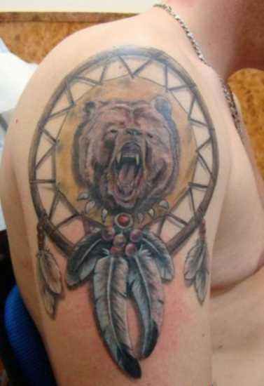 A tatuagem no ombro de um cara - apanhador de sonhos com o urso