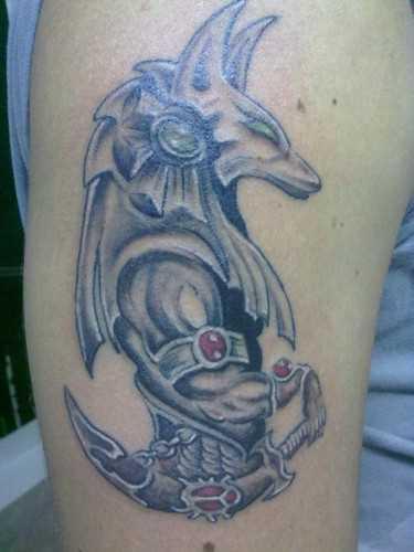 A tatuagem no ombro de um cara com a imagem de anubis