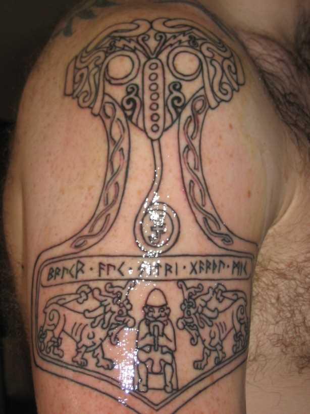 A tatuagem no ombro de um cara com a imagem de um martelo