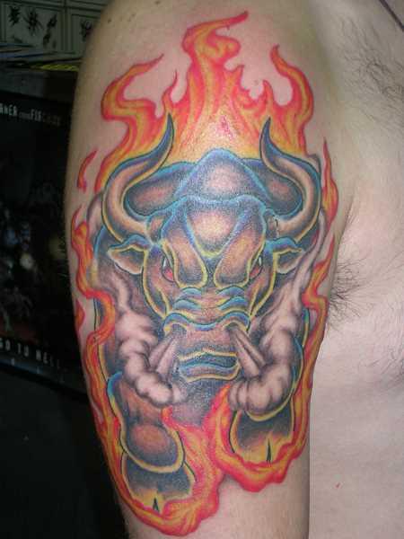A tatuagem no ombro de um cara com a imagem de um touro