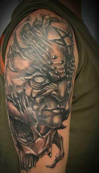 A tatuagem no ombro de um cara com a imagem do diabo