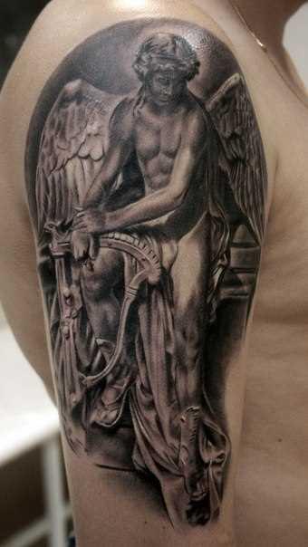 A tatuagem no ombro de um cara - de- anjo com harpa