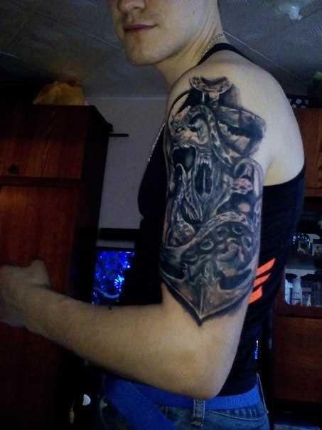 A tatuagem no ombro de um cara de crânio e âncora