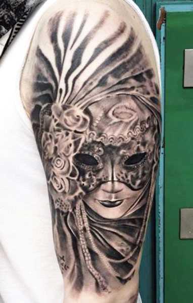 A tatuagem no ombro de um cara em forma de menina na máscara