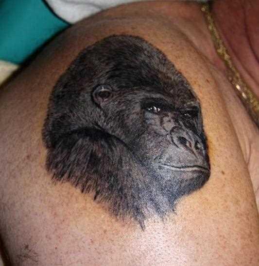 A tatuagem no ombro o homem - macaco