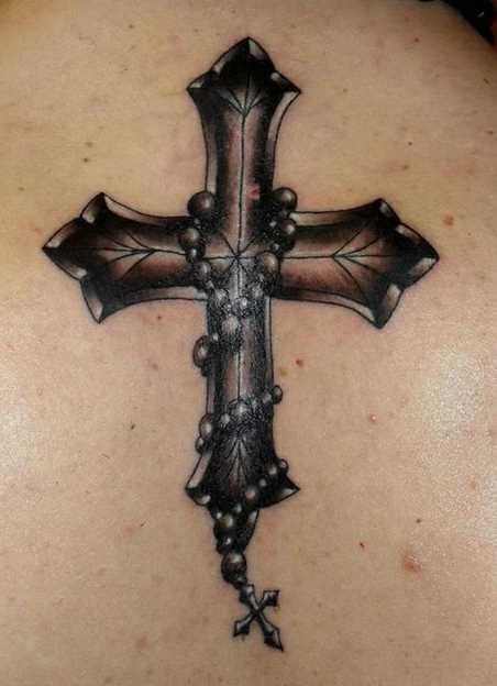 Bela tatuagem na coluna da menina - a cruz e a cruz na cadeia