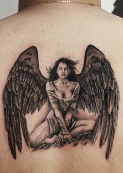 Bela tatuagem na parte de trás, a menina - anjo em forma de menina bonita