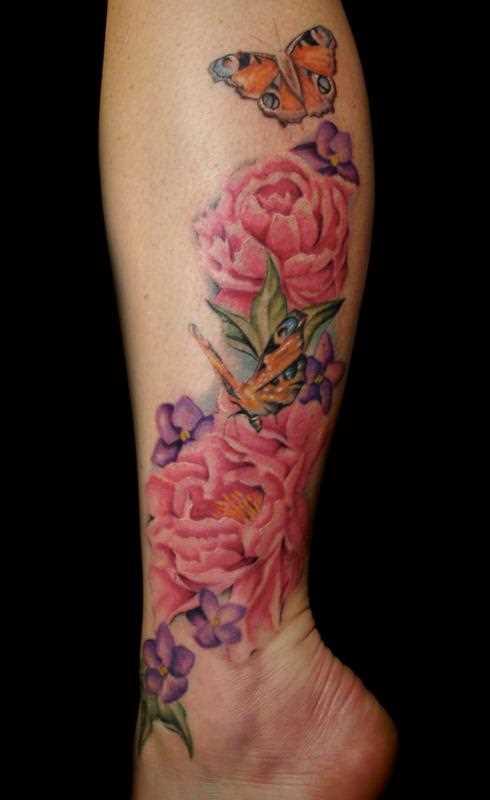 Bela tatuagem na perna da menina - peônias e borboleta