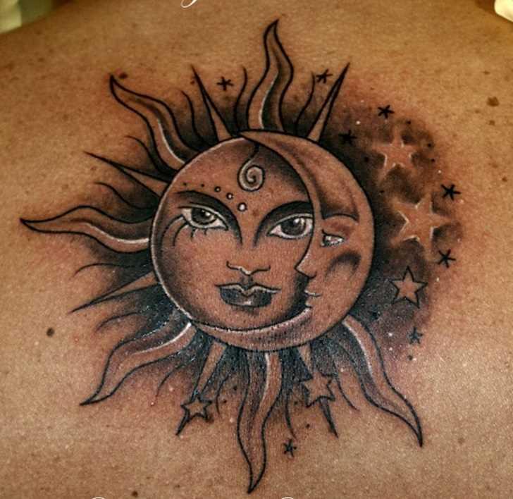Bela tatuagem nas costas do cara - o sol, a lua e as estrelas