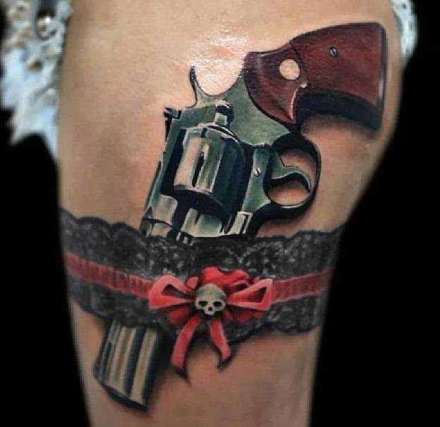 Bela tatuagem nas coxas da menina - a arma e a liga