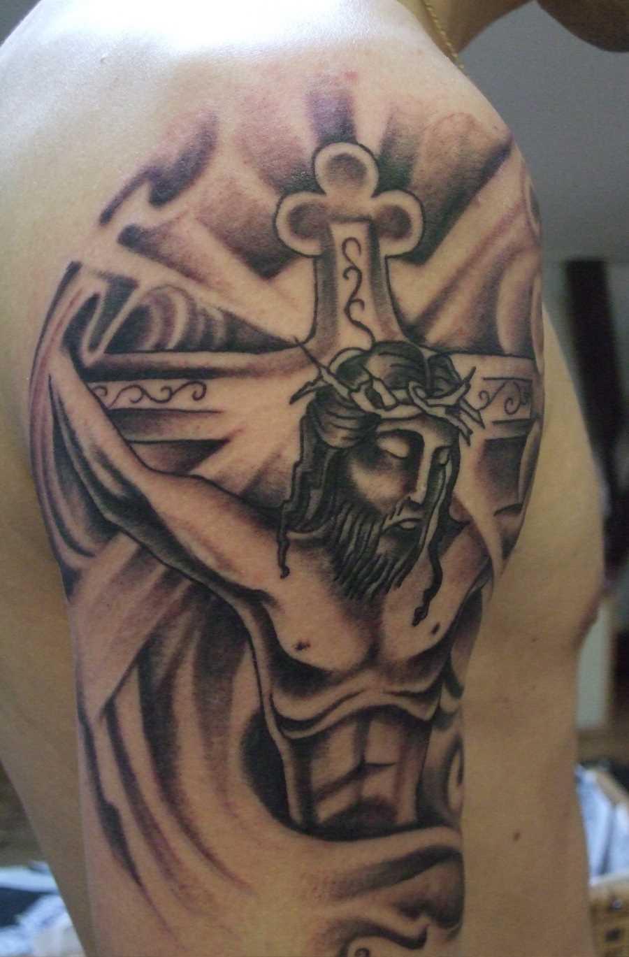 Bela tatuagem no ombro de um cara em forma de uma cruz e de Jesus crucificado