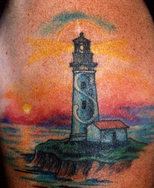 Bela tatuagem no ombro de um cara - um farol e um chalé à beira-mar