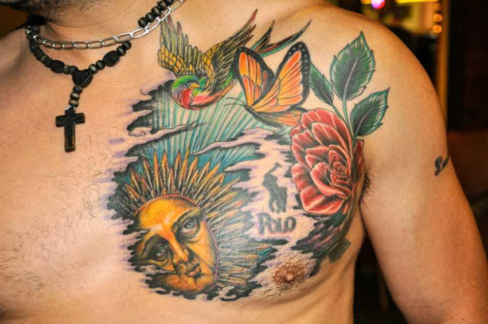 Bela tatuagem no peito de um cara - de- sol, uma rosa, borboleta e a andorinha