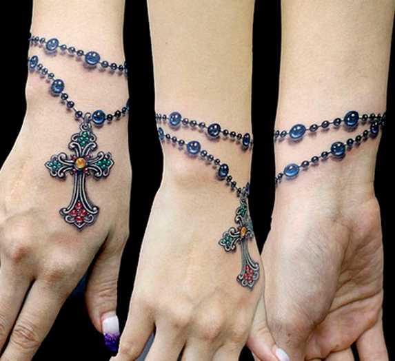 Bela tatuagem no pulso da menina - um colar com uma cruz