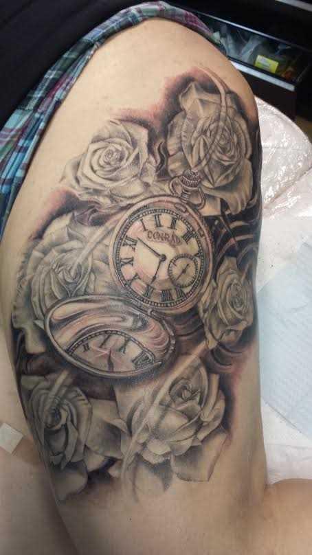 Bela tatuagem que tem no braço da menina - relógio de bolso e rosas