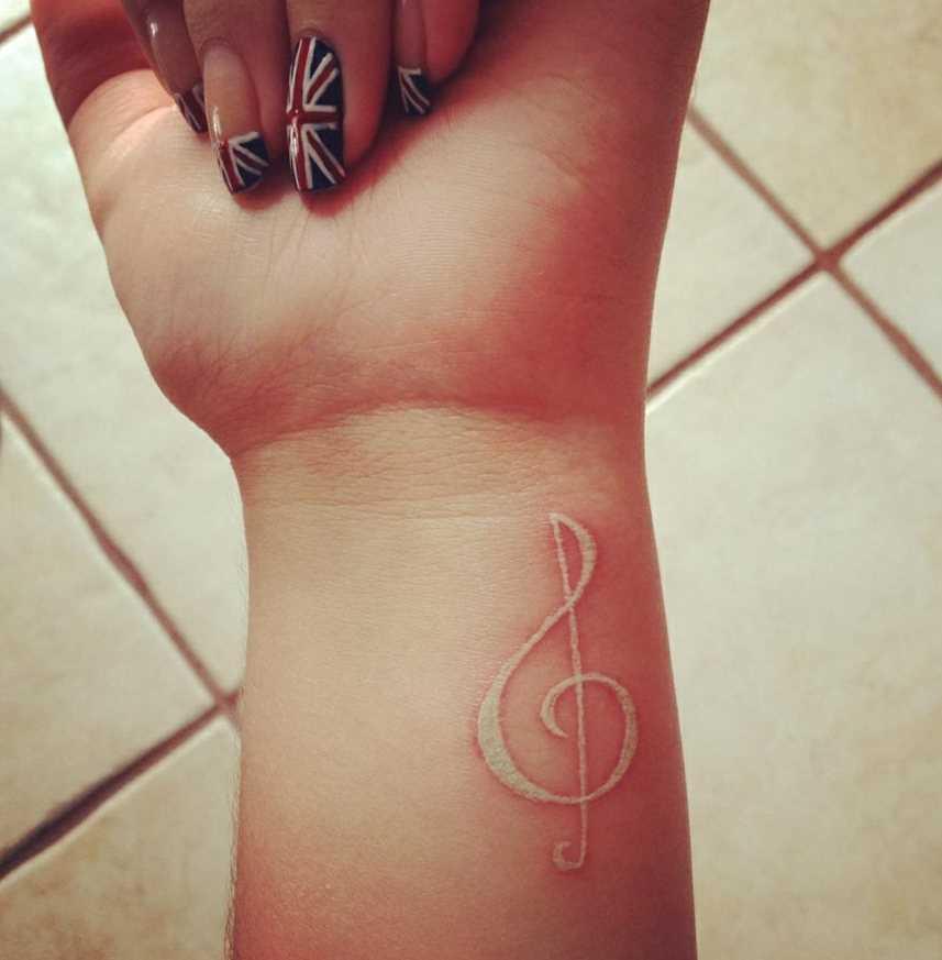 Branco tatuagem no pulso da menina - clave de sol