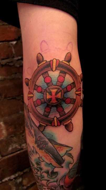 Cores de tatuagem do volante no cotovelo do cara