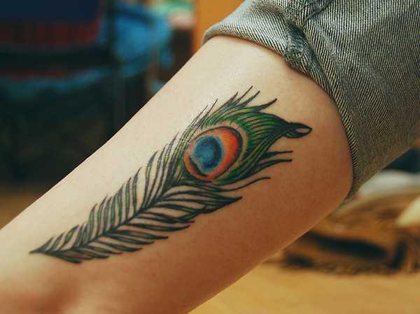 Cores de tatuagem que a menina no ombro em forma de caneta pavão