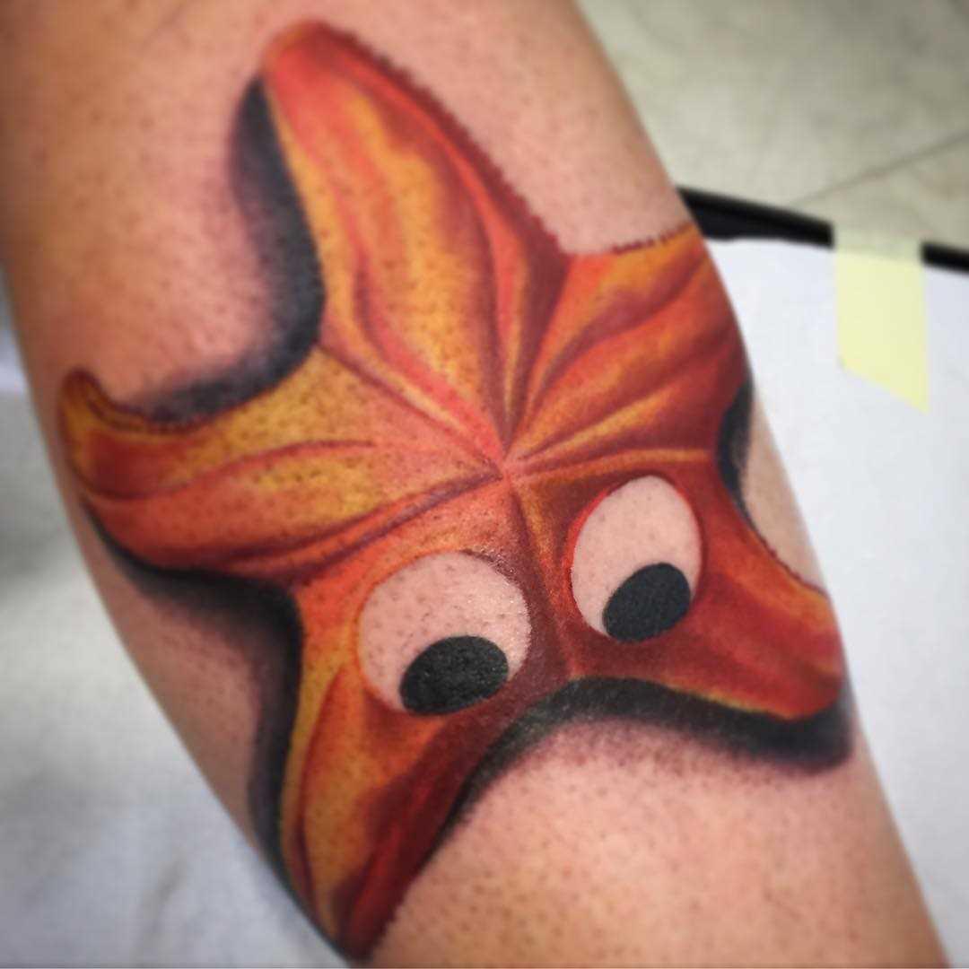 De laranja, a tatuagem de estrela do mar com os olhos sobre a perna da menina