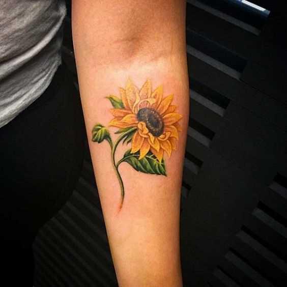 Esta foto de uma linda tatuagem de girassol no antebraço da menina