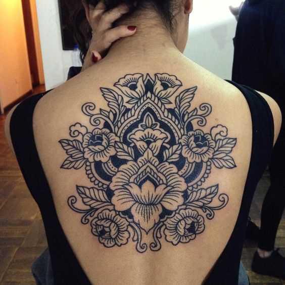 Esta foto de uma linda tatuagem no estilo de um gráfico na parte de trás da menina