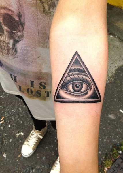 Figura amuleto olho que tudo vê no antebraço da menina
