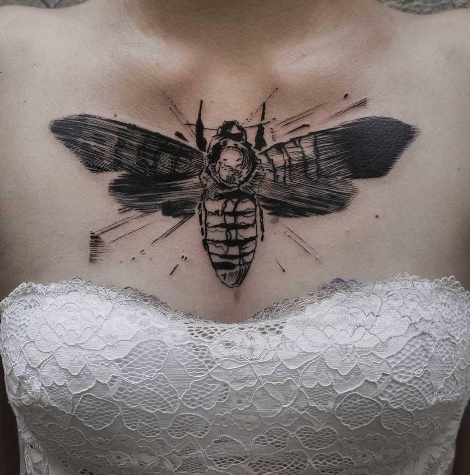 Figura inseto no peito de uma mulher