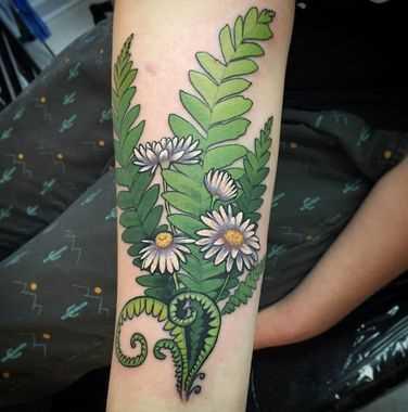 Foto a cores da tatuagem de margaridas no antebraço da menina