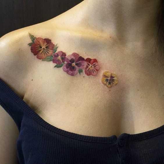 Foto a cores da tatuagem de violetas na clavícula menina