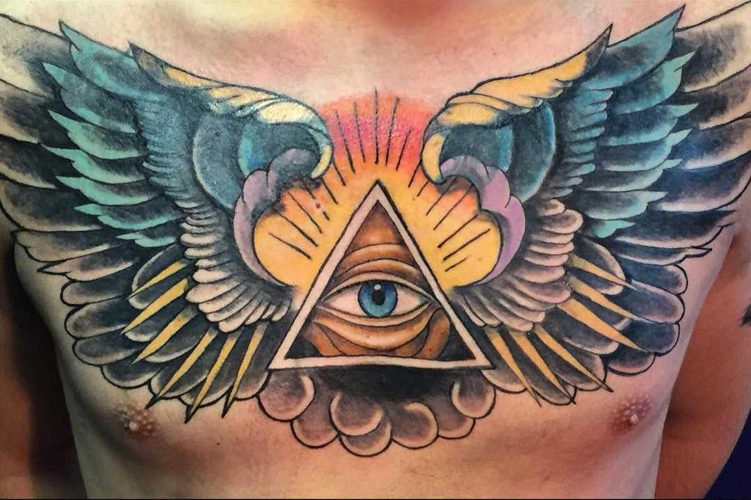 Foto a cores da tatuagem que tudo vê piscar de olhos com asas no peito do cara